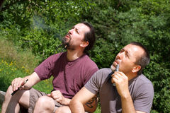 2 men smoking e-cigarettes in nature Royalty Free Stock Images