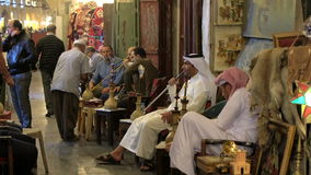 Men smoking Sheesha or water pipes in cafe at Souq Waqif, Doha stock video footage