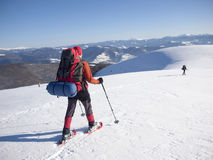 Men in snowshoes go in the mountains. Royalty Free Stock Photos