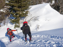 Men in snowshoes go in the mountains. Stock Photography