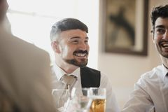 Men Socialsiing At Wedding Reception. Close up shot of a best men at a wedding, socialising with the guests at the reception stock image