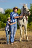 The man with the son in hats on walk with a white horse. The men with the son in hats and blue shirts on walk with a white horse stock photography
