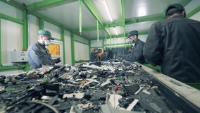 Men sort metal garbage on a conveyor. Recycle process, secondary use of plastic. Trash, e-waste, electronic garbage