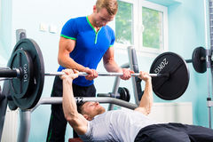 Men in sport gym training with barbell. For fitness Royalty Free Stock Photo
