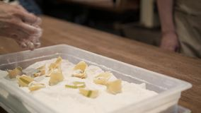 Men sprinkling tortellini with flower and putting them in a wooden box. Hands of two unrecognizable men sprinkling tortellini with flower and putting them in a stock video footage