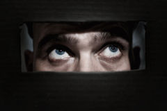 Men spying through a hole. Male eyes spying through a hole in the wall royalty free stock image