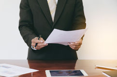 Men standing at desk and reading document hand close up. stock images