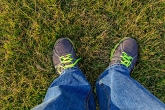 Men standing on the grass in jeans and sneakers Royalty Free Stock Photo