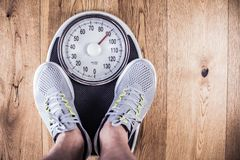 Men standing on weigh scales at gym.Waist measurement by tape measure .Concept of healthy lifestyle. royalty free stock photos