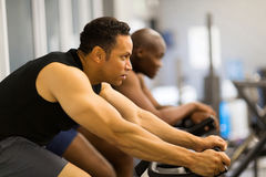 Men stationary bike. Fitness men working out with stationary bike in gym Stock Photography