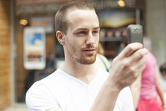 Men on street photographing with mobile phone Royalty Free Stock Photos