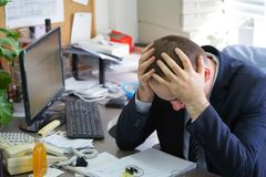 Men stressed out at work. Close-up of an office worker. A man in stress in front of a computer. Poor economy concept. Face expression, emotion Stock Images