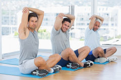 Men stretching on mats in fitness class Stock Photo