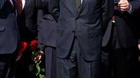 Men in strict black suits with red flowers. Company management. The official delegation stock photos