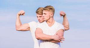 Men strong muscular athlete bodybuilder posing confidently in white shirts. Sport lifestyle and healthy body. Attractive. Twins. Handsome strong twins. Men stock images