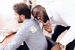 The men stuck a sticker on the back of another man. This is his business colleagues. They joked at him on April 1st Stock Photography