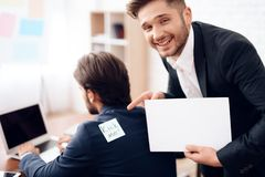 The men stuck a sticker on the back of another man. This is his business colleagues. They joked at him on April 1st Stock Image