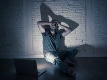 Men suffering Internet cyber bullying sitting alone with computer feeling hopeless. Severely distraught young man with laptop suffering cyberbullying and royalty free stock image