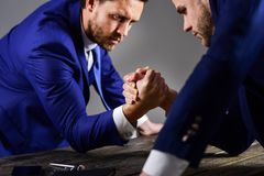 Men in suit or businessmen with tense faces compete. In armwrestling on table on dark background. Business rivalry concept. Businessmen fighting for leadership Royalty Free Stock Image