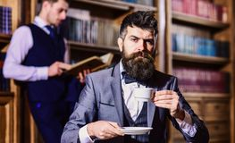 Men in suit, detectives spend leisure in library. Private investigator and detective concept. Man with beard and strict face at tea party. Retro detectives royalty free stock photography
