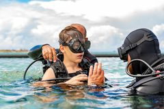 A man in a suit for diving prepares a boy to dive. A men in a suit for diving prepares a boy to dive royalty free stock image