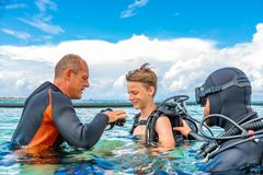 A man in a suit for diving prepares a boy to dive stock photos