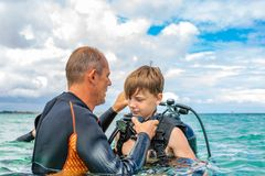 A man in a suit for diving prepares a boy to dive stock photography