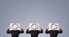 Men in suit gesturing with sketched smiley faces on cardboard Stock Images