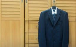 Men suit jacket hanging in closet wardrobe. Men suit jacket hanging in closet wardrobe Stock Photography