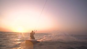 A pair of divers swim in the sea at dawn, slow motion. Men in suits for diving are kitesurfing at dawn stock video footage