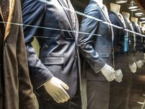 Men Suits, with shirts, ties, pants and blue jackets on display on dummies in front of a tailor store, on a window. It is one of the main formal garments in stock photo