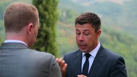 Men in suits talking in the garden.  stock video footage