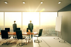 Men in sunny conference room with furniture and cityview Stock Photos