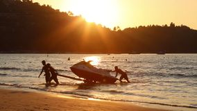 Men at sunset pull hydro cycle out of the water on a sandy beach.  Summer vacation. Water bike loading in to  trailer