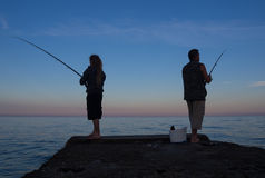 Men at sunset to catch the bait fish from the pier Stock Photos