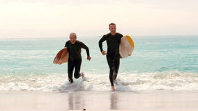 Men with surfboards running. Out of the water stock video