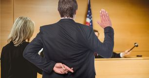 Men swearing in the judge with fingers crossed Stock Photo