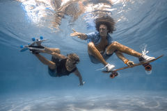 Men in the swimming pool. Men skateboarding underwater in the swimming pool Stock Photography