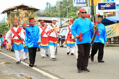 Men with swords from Maluku Utara. Men with traditional swords from Maluku Utara dressed in traditional clothes and parade float with hut in procession in Royalty Free Stock Images