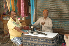 Men at a table with an old sewing machine, Delhi Stock Image