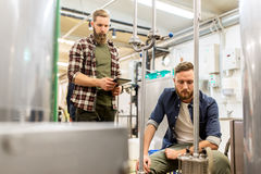Men with tablet pc at craft beer brewery filter. Alcohol production, business and people concept - men with tablet pc computer at craft beer brewery filter Royalty Free Stock Photo