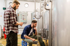 Men with tablet pc at craft beer brewery kettle. Alcohol production, business and people concept - men with tablet pc computer at craft beer brewery kettle Royalty Free Stock Photo