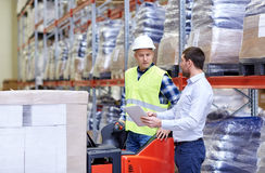 Men with tablet pc and forklift at warehouse Royalty Free Stock Photography