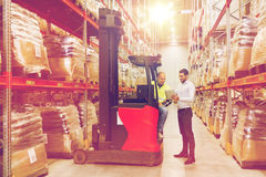 Men with tablet pc and forklift at warehouse. Wholesale, logistic, loading, shipment and people concept - loader on forklift and businessman with tablet pc Stock Images