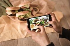 Men take photo of hamburgers. Smart man take photo of burger on his telephone. Humburger with meal Stock Image