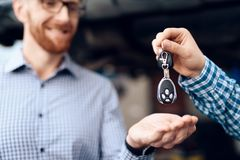 The man takes his car from the auto service. The mechanic transfers the car keys to the customer stock image