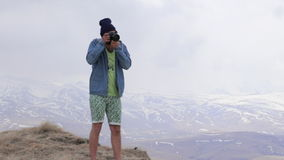 Men takes pictures of the mouintains landscape. stock video footage