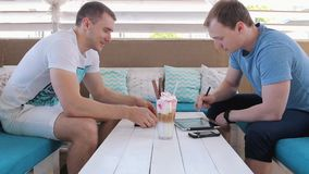 Men talk in a cafe and work with tablets. Men talking in a cafe at a table opposite each other stock footage