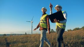 Men talk while checking windmills, close up. Renewable enrgy concept. stock video footage