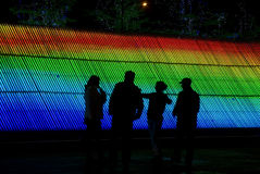 Men talking in front of colorful light. In square Stock Image